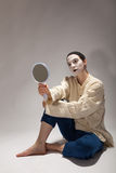 The clown is sitting on the ground with a mirror in his hand Stock Photography