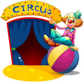 A clown sitting at the top of a ball pointing the circus house Royalty Free Stock Photos
