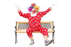 Clown som gör en gest lycka som placeras på bänk Arkivbild