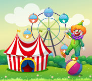 A clown standing above the ball at the carnival Royalty Free Stock Image