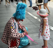 The clown on the street. The buffoon is making balloon toy on the street in shenzhen royalty free stock photography