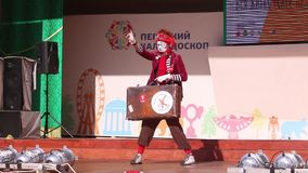 Clown with suitcase on open air stage stock video