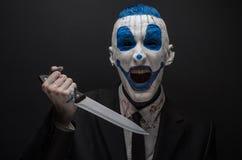 Clown terrible et thème de Halloween : Clown bleu fou dans un costume noir avec un couteau dans sa main d'isolement sur un fond f Photographie stock libre de droits