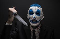 Clown terrible et thème de Halloween : Clown bleu fou dans un costume noir avec un couteau dans sa main d'isolement sur un fond f Photos stock