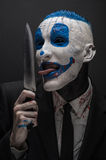 Clown terrible et thème de Halloween : Clown bleu fou dans un costume noir avec un couteau dans sa main d'isolement sur un fond f Images libres de droits