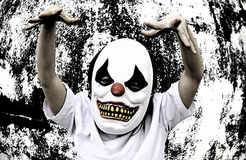 Clown Terror Scare. Crazy clown mask halloween costume and fear stock photo