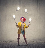 Clown throwing bulb lights. Clown girl throwing in the air bulb lights Stock Photos