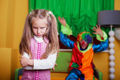 Clown tries to cheer up a sad girl. Royalty Free Stock Image