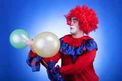 Clown with two balloons in hand on blue background Royalty Free Stock Photography