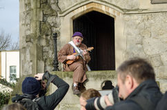Clown with ukelele. HACKNEY, LONDON - FEBRUARY 7, 2016:  A clown playing a ukelele poses for photographers outside All Saints Church in Haggerston ahead of the Royalty Free Stock Photos