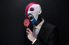 Clown- und Halloween-Thema: Furchtsamer Clown mit dem rosa Haar in einer schwarzen Jacke mit Süßigkeit in der Hand auf einem dunk Lizenzfreie Stockfotos