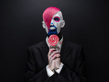 Clown- und Halloween-Thema: Furchtsamer Clown mit dem rosa Haar in einer schwarzen Jacke mit Süßigkeit in der Hand auf einem dunk Stockfotos