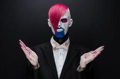 Clown- und Halloween-Thema: Furchtsamer Clown mit dem rosa Haar in einer schwarzen Jacke mit Süßigkeit in der Hand auf einem dunk Stockfoto