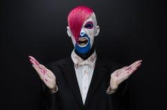 Clown- und Halloween-Thema: Furchtsamer Clown mit dem rosa Haar in einer schwarzen Jacke mit Süßigkeit in der Hand auf einem dunk Lizenzfreie Stockfotografie
