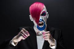 Clown- und Halloween-Thema: Furchtsamer Clown mit dem rosa Haar in einer schwarzen Jacke mit Süßigkeit in der Hand auf einem dunk Lizenzfreies Stockbild