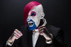Clown- und Halloween-Thema: Furchtsamer Clown mit dem rosa Haar in einer schwarzen Jacke mit Süßigkeit in der Hand auf einem dunk Stockbilder