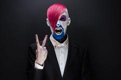 Clown- und Halloween-Thema: Furchtsamer Clown mit dem rosa Haar in einer schwarzen Jacke mit Süßigkeit in der Hand auf einem dunk Lizenzfreie Stockbilder
