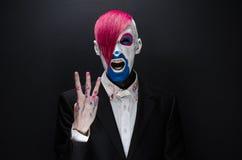 Clown- und Halloween-Thema: Furchtsamer Clown mit dem rosa Haar in einer schwarzen Jacke mit Süßigkeit in der Hand auf einem dunk Lizenzfreies Stockfoto