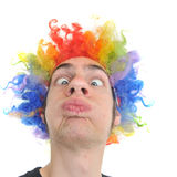 Clown Wig. A white Caucasian young adult wearing a silly clown wig with rainbow colorful hair Stock Photography