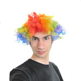 Clown Wig. A white Caucasian young adult wearing a silly clown wig with rainbow colorful hair Stock Image