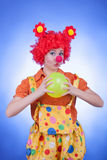 Clown woman with a ball on blue background Royalty Free Stock Image