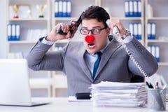 Clownaffärsman som arbetar i det ilskna frustrerat för kontor med a arkivbild
