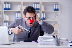 Clownaffärsman som arbetar i det ilskna frustrerat för kontor med a arkivfoton