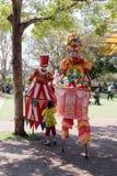 Clowne auf Stelzen grüßen einen kleinen Besucher zum Anziehungskraftpark lizenzfreie stockbilder