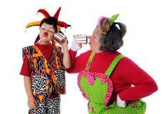 Clowne, die Blechdose-Telefone verwenden Stockfoto