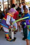 Clownen Inflates ballongen för unge på festivalen royaltyfri foto