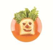 Clownframsida av en skiva av bröd, grönsallathår, röd näsa Arkivbild