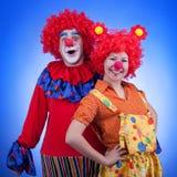 Clownpaar in kostuums op blauwe achtergrond Royalty-vrije Stock Foto