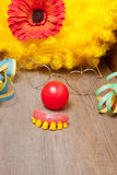 Clowns costume with teeth. Utensils of a clowns costume laying on a wooden board Royalty Free Stock Photography