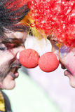 Clowns Face Off. A Couple Of Colorful Circus Clowns Stand Outside Opposite Each Other Head To Head In A Conflicting Confrontational Face Off Royalty Free Stock Image