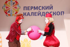 Clowns hold ball on open air stage Royalty Free Stock Photos