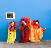 Clowns in masks performing. Three white clowns in the yellow, red, and orange Traditional Clothing are performing in front of blue wall with small window Stock Images