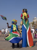 Clowns in South African Flags. Two clowns, one on stilts, in South African colors, are entertaining visitors to the Soccer World Cup 2010 at the beachfront royalty free stock photography