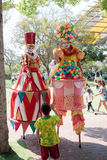 Clowns on stilts greet a small visitor to attractions park Stock Photography