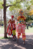 Clowns on stilts greet a small visitor to attractions park Royalty Free Stock Images