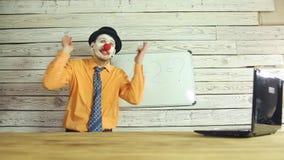 Clownzakenman die in het bureau werken stock videobeelden