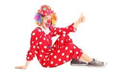 Clownzitting op de vloer en het opgeven van duim Royalty-vrije Stock Fotografie