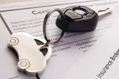 Clés de véhicule sur des documents d'assurance Images stock