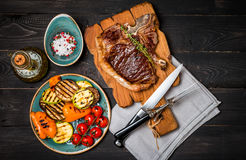 Club Beef steak with seasonings and Grilled vegetables. On cutting board on dark wooden background, top view Stock Image
