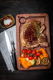 Club Beef steak with seasonings and Grilled vegetables. On cutting board on dark wooden background, top view Royalty Free Stock Photo