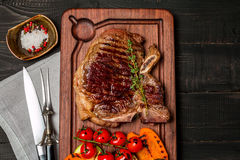 Club Beef steak with seasonings and Grilled vegetables. On cutting board on dark wooden background, top view Royalty Free Stock Photos