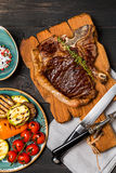 Club Beef steak with seasonings and Grilled vegetables. On cutting board on dark wooden background, top view Royalty Free Stock Photography