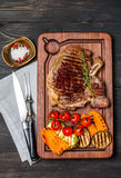 Club Beef steak with seasonings and Grilled vegetables. On cutting board on dark wooden background, top view Royalty Free Stock Images