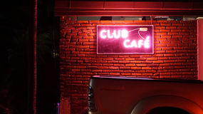 Club and cafe neon light pink sign. On red brick wall Stock Photos