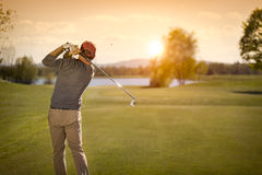 Club de golf de balanceo masculino del jugador de golf en la oscuridad Fotografía de archivo