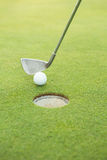 Club de golf mettant la boule au trou Photo libre de droits